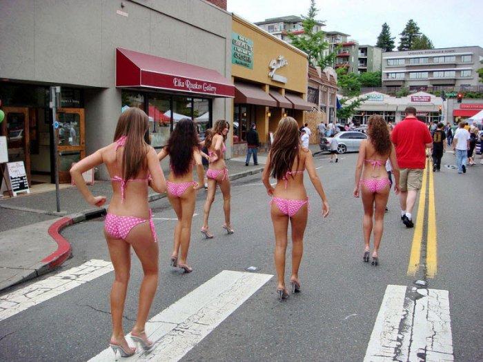 девушки в розовых купальниках на каблуках шагают по улице