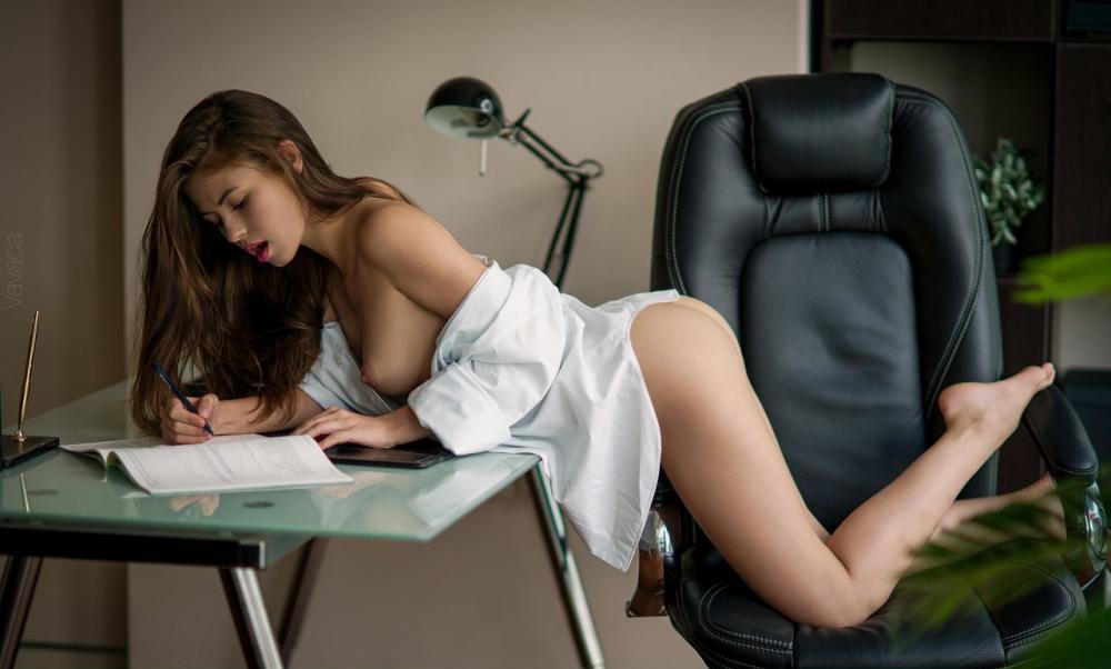 Офисные девушки эротика почти голая раком в черном офисном кресле немного прикрыта белой длинной рубашкой, что то пишет в журнале