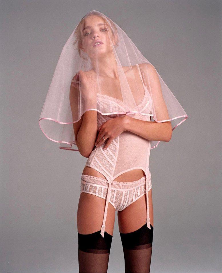 модель наталья водянова стоит в розовой грации черных чулках на поясе, трусиках, сверху наброшена фата невесты, стоит с томным взглядом приоткрыв ротик
