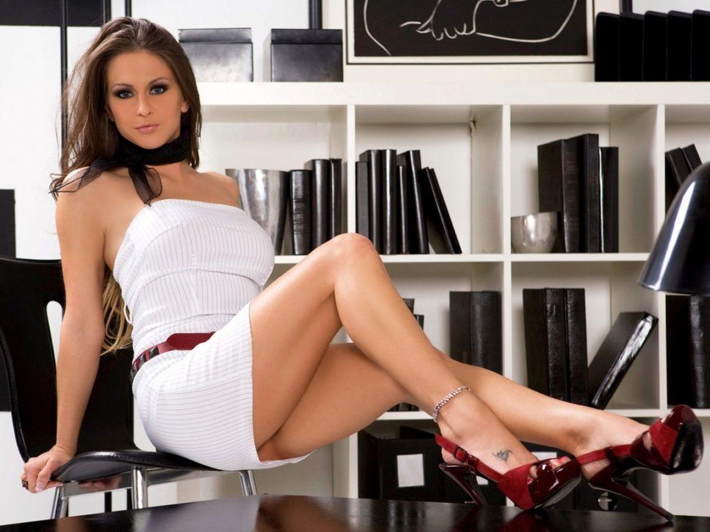 Сексуальная офисная девушка в белом коротком платье с открытыми плечами, с черным платком на шее, в босоножках оголила свои красивые ножки с тату на ступне и браслетом