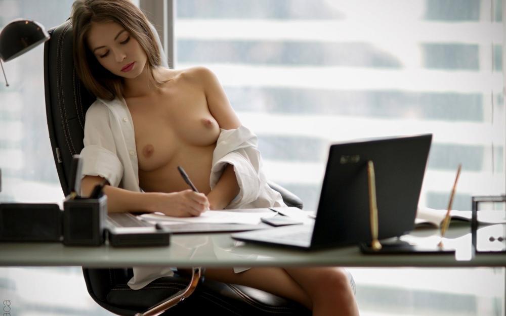 Сексуальная офисная девушка в расстегнутой белой мужской рубашке сидит в офисном кресле,что то пишет, оголив свою маленькую красивую грудь