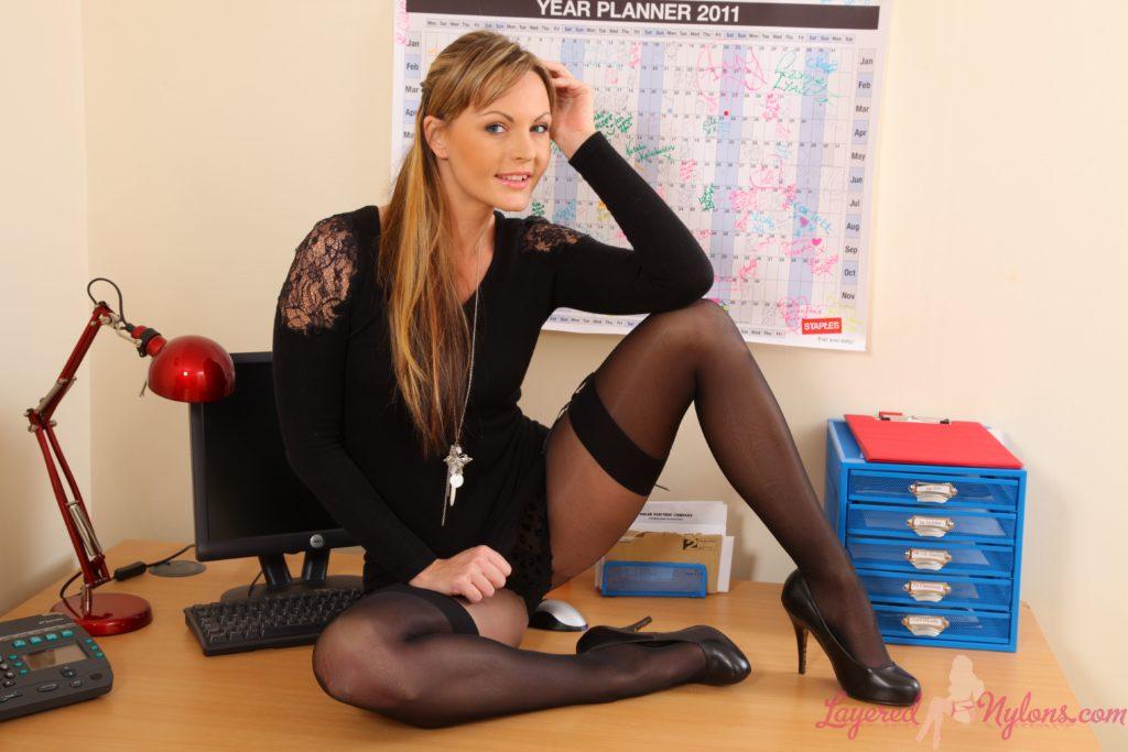 Девушка на офисном столе сидит блондинка с длинным волосом раздвинув ноги в чулках на каблуках