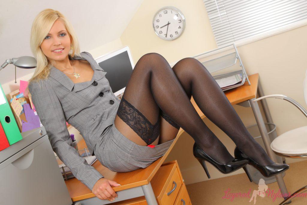 Девушка на офисном столе блондинка в сером костюме, в чулках, туфли на каблуке подняла ноги согнув в коленях