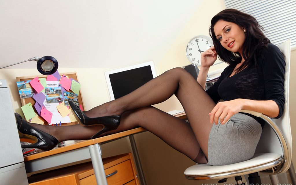 Сексуальная офисная девушка сидит в короткой светлой юбке на стуле в черных колготах ноги закинула на стол, туфли на высоком каблуке