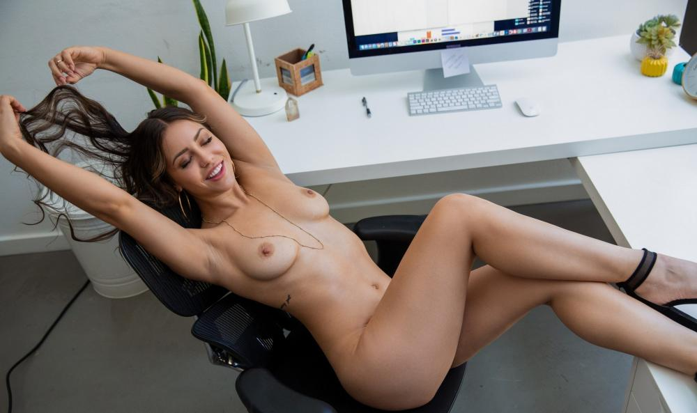 Сексуальная офисная девушка голая в босоножках потягивается в кресле, ноги закинула на стол