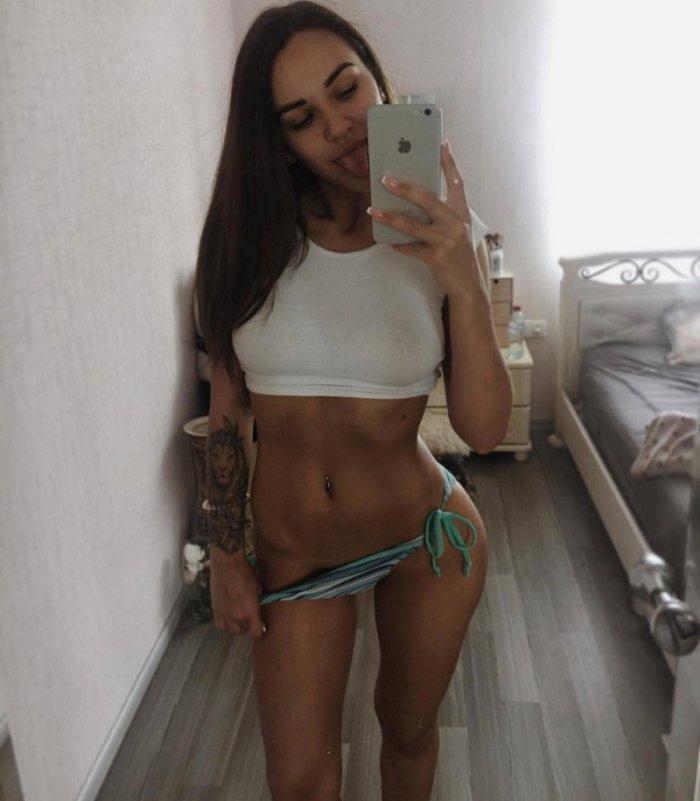 фото девушек без лифчика в коротком белом топике и трусиках бикини стоит возле кровати делает селфи