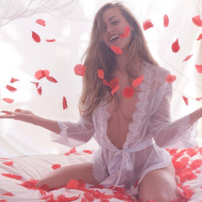 фото девушек без лифчика в прозрачном распахнутом светлом пеньюаре сидит на коленях, сверху сыпятся лепестки красных роз