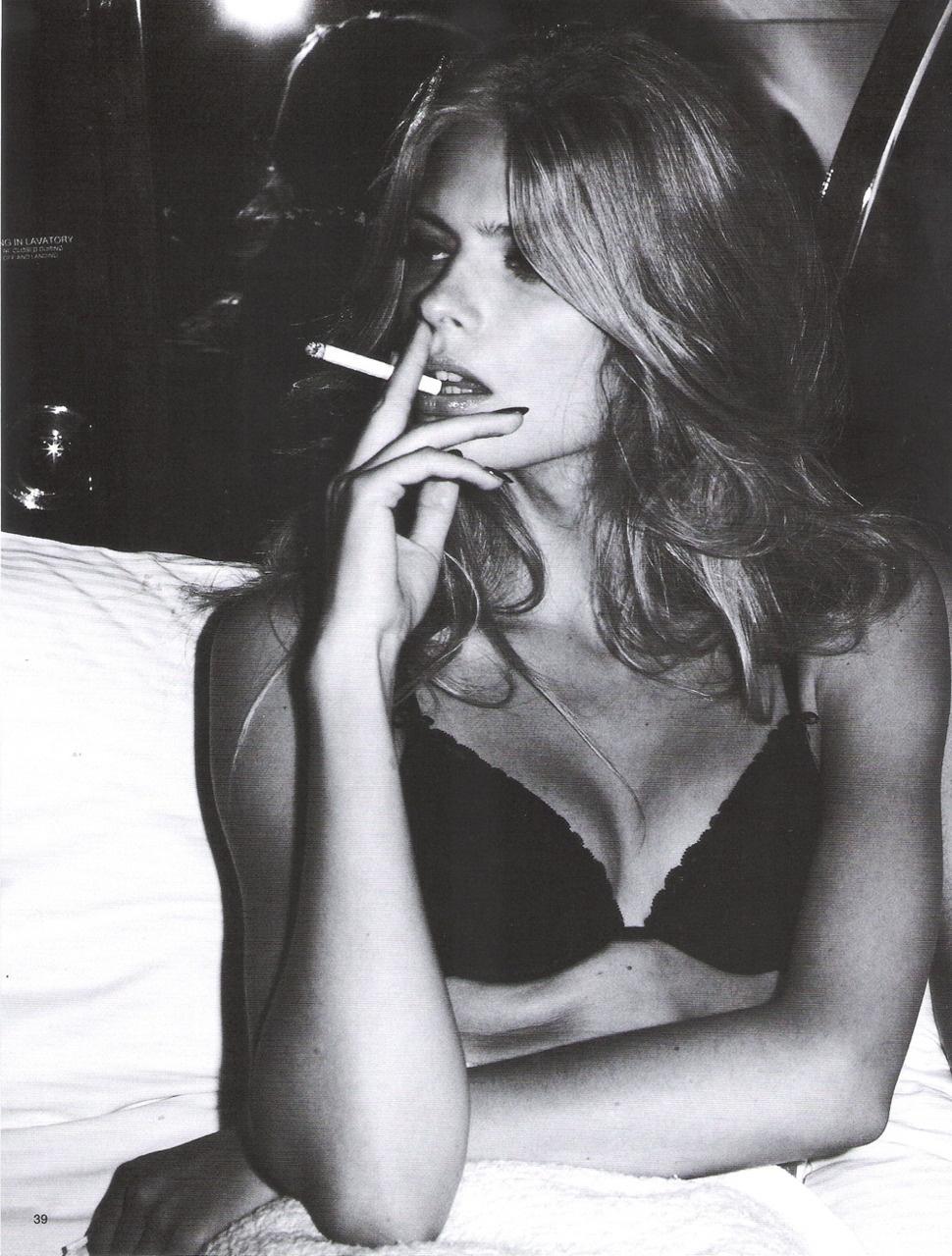 Лицо девушки с сигаретой у губ в черном бюстике, фото черно белое