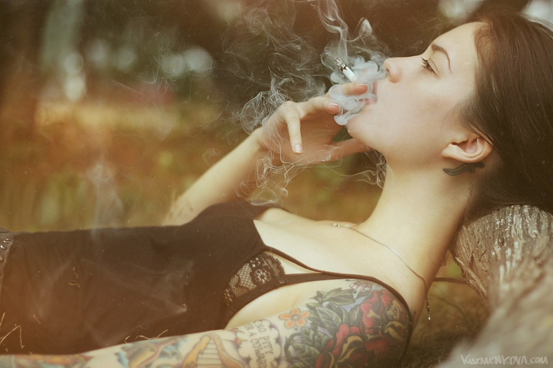 девушка курит лежа на кровати в черном пеньюаре, затягивается дымом, на левом плече цветная татуировка на всю длину руки