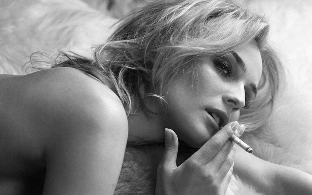 красивая женщина блондинка курит в кровати, голые плечи