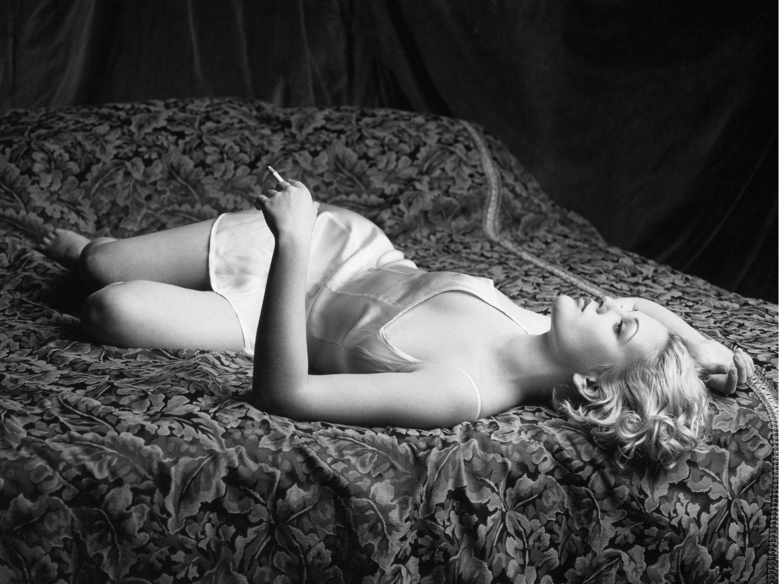 девушка курит сигарету блондинка в светлом коротком пеньюаре на спине на кровати лежит