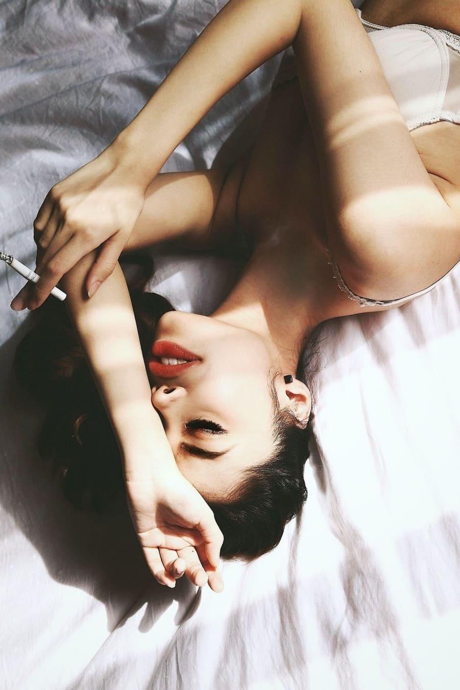 девушка курит лежа на спине в постели красивые яркие губы, закрытые глаза, рот немного приоткрыт, в правой руке сигарета