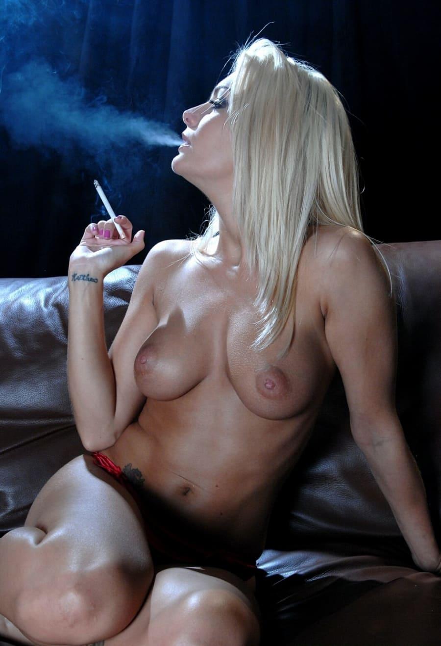 Красивая голая блондинка сидя на кожаном диване выдыхает дым от сигареты