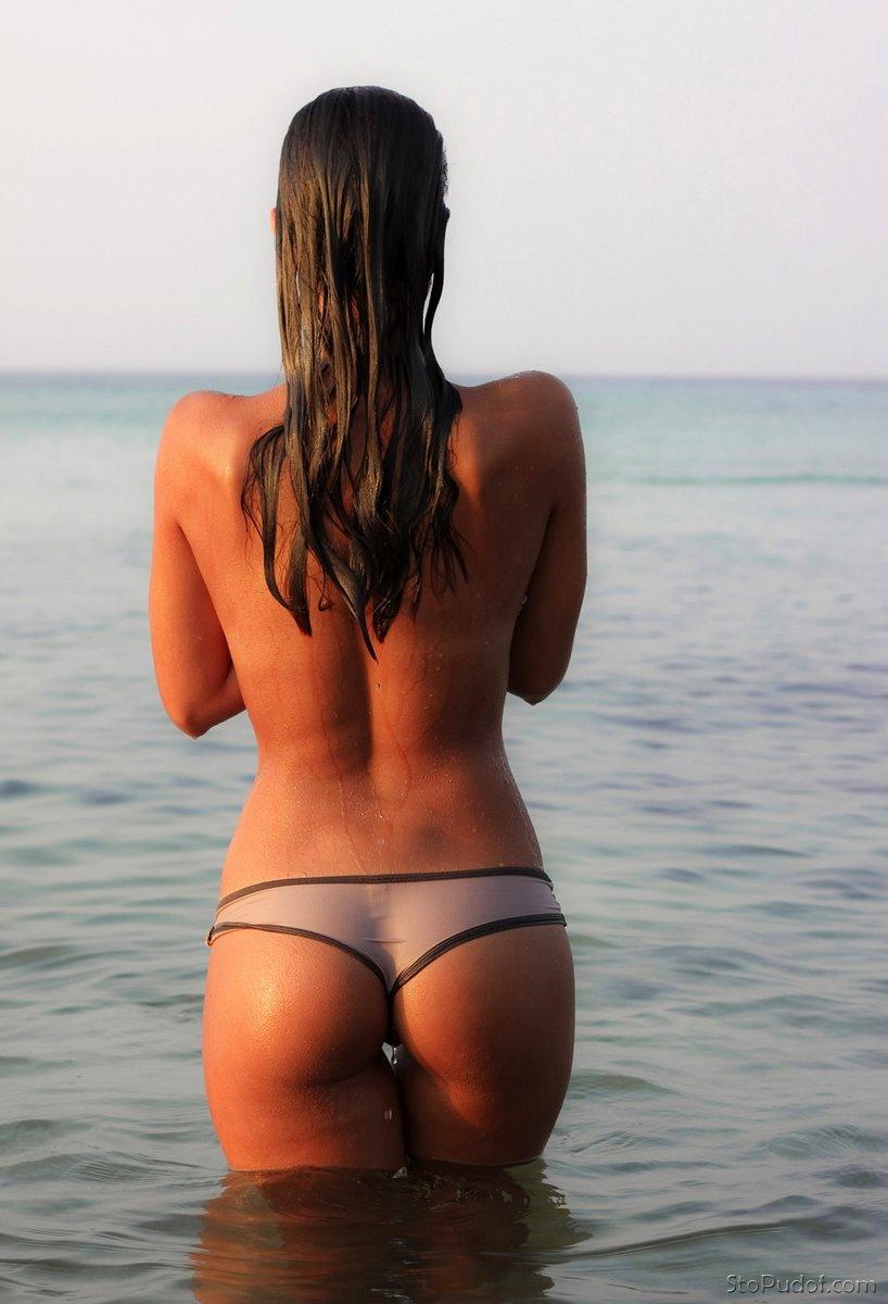 Женщина с маленькой жопой в серых трусиках стоит в воде, волосы длинные распущены