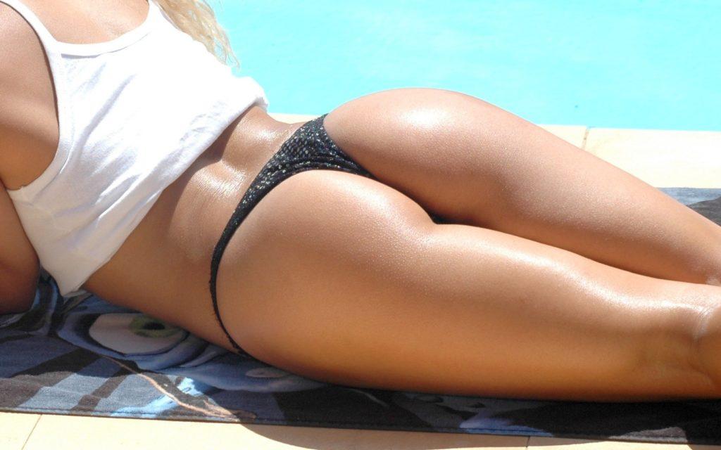 Женщина с узкой попой лежит на берегу бассейна