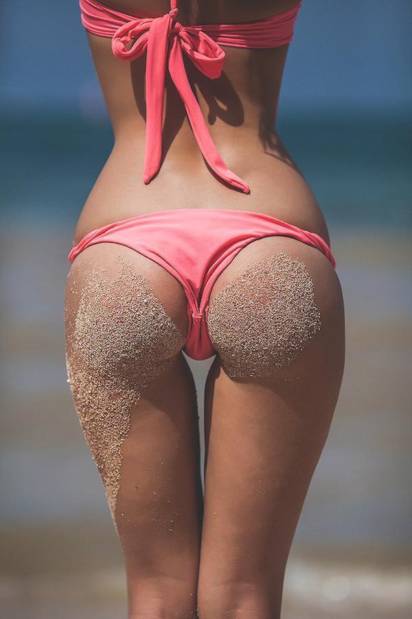 Красивая женская попа в розовых трусиках с песком от сидения на пляже на ягодицах и ляжке