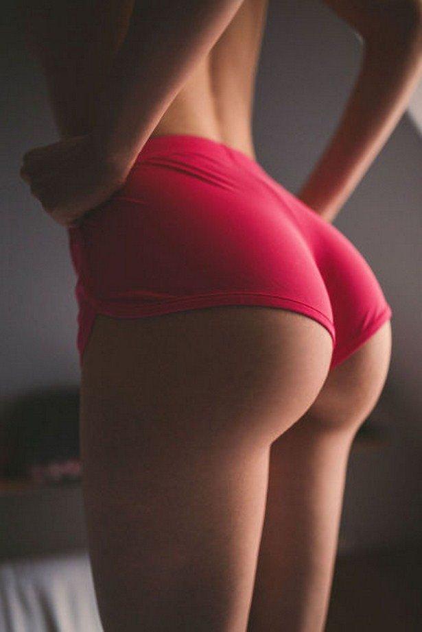Женщина показывает жопу в красных спортивных трусах