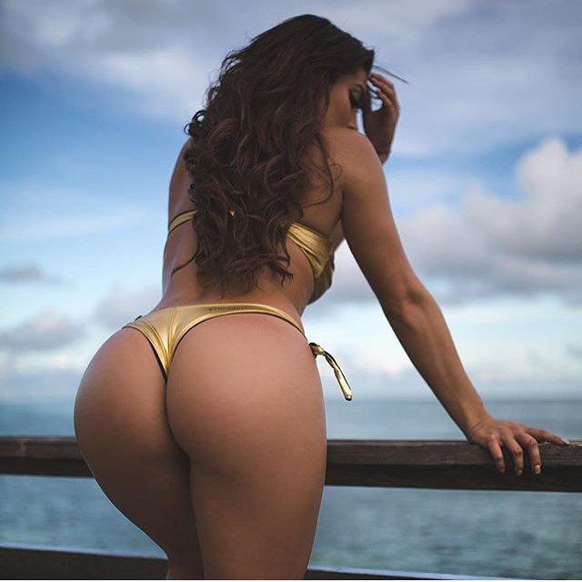 Женщина стоит на деревянном пирсе в золотистом купальнике показывает жопу на закате