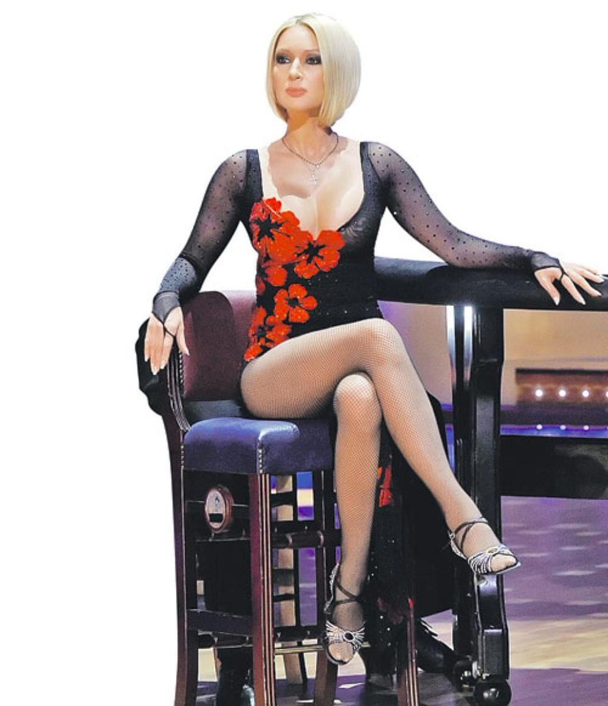 Лера Кудрявцева фото с короткой стрижкой сидит на стуле в боди черного цвета с длинным рукавом и красными маками, колготки с рисунком, босоножки на высоком каблуке, красивые стройные ножки