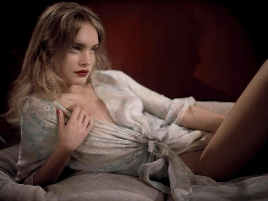 модель наталья водянова фото молодой лежит на кровати в распахнутом светлом пеньюаре, на губах яркая помада, волосы распущены