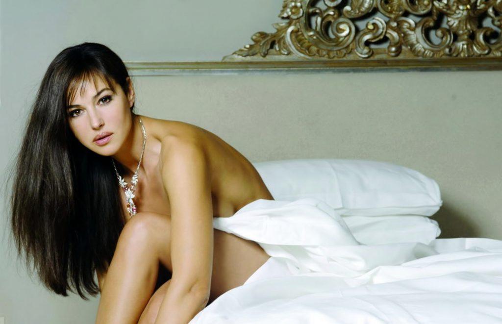 фото Моники Беллуччи на кровати устеленной белыми простынями сидит обнаженная слегка прикрывшись, волосы распущены, на шее ожерелье, макияж яркий