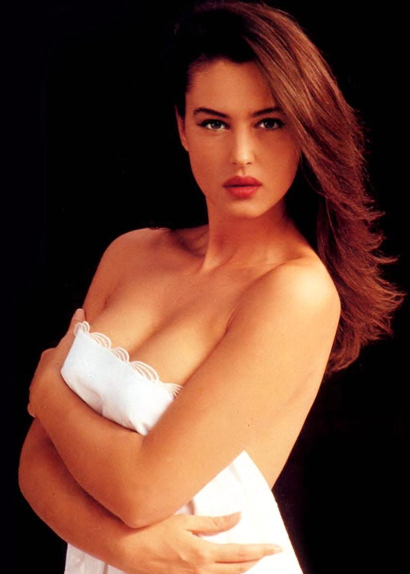 эротическая Моника Беллуччи голая по пояс стоит прикрывшись немного белым покрывалом