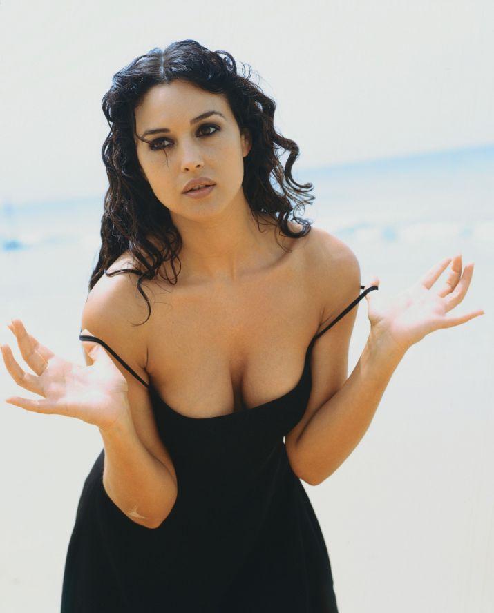 эротическая Моника Беллуччи фото стоит в черном платье немного согнувшись вперед снимает тонкие бретельки показывает глубокое декольте с сиьками