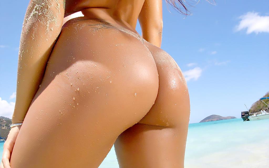 женская попа фото на пляже красивые ягодицы слегка в песке, на пояснице видна татуировка