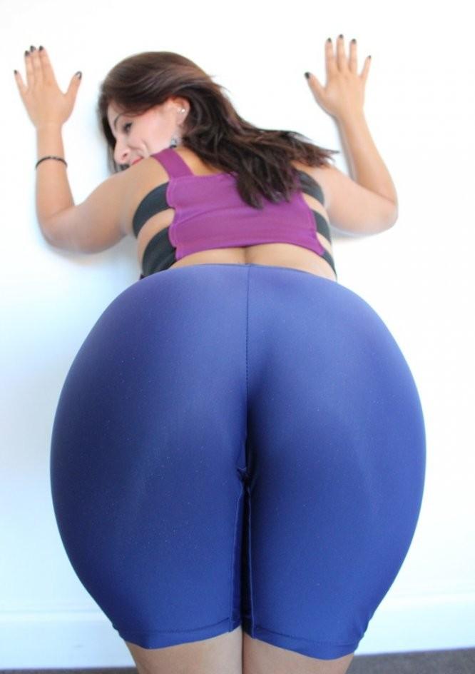 Зрелые женщины с большой попой стоит у стены согнувшись, руки положила на стенку в коротких панталонах синего цвета