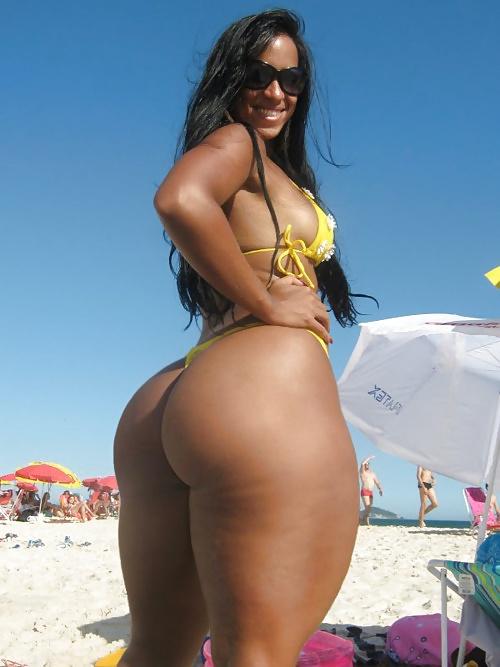 Зрелые женщины с большими попами стоит вполоборота на пляже в бикини загорелая бразильянка с шикарными формами
