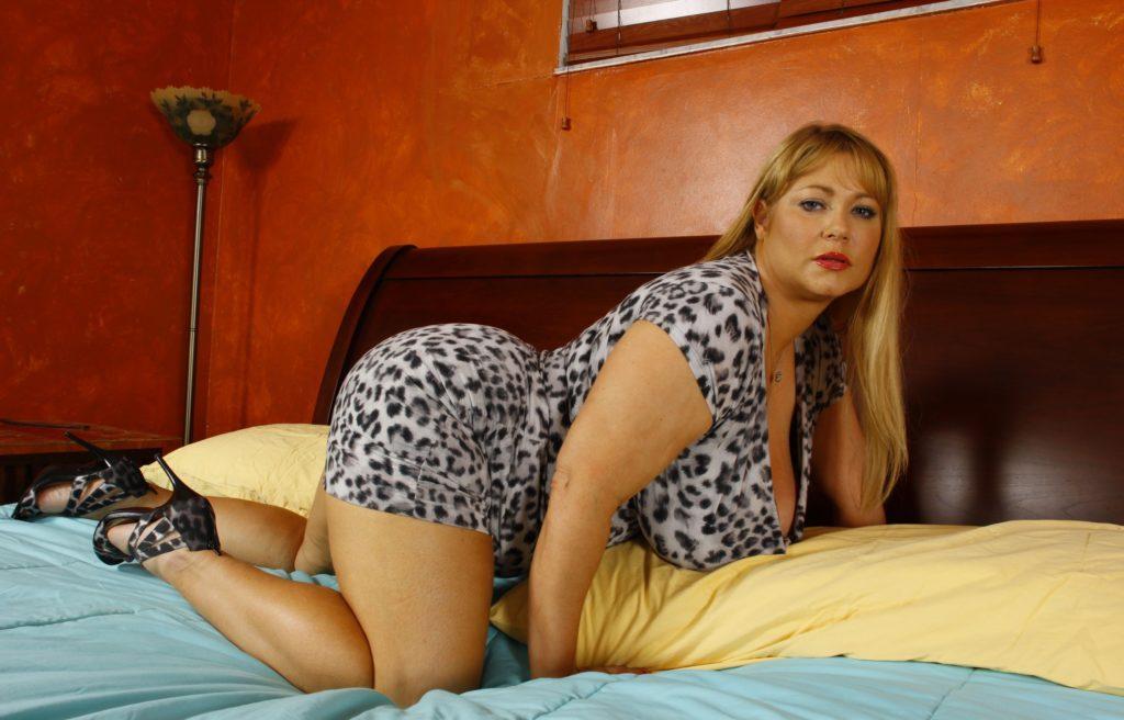 Большие попы зрелых женщин стоит на коленях на кровати красивая блондинка в коротком леопардовом платье с шикарными формами огромными сиськами в закрытых босоножках