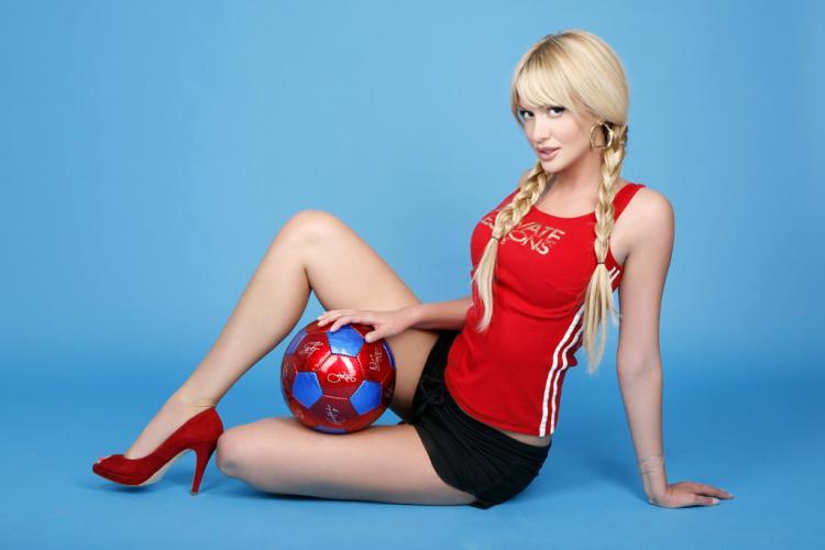 Виктория Лопырева фото в красной майке черных спортивных шортах, красные туфли на каблуке сидит на полу зажав между ног футбольный мяч