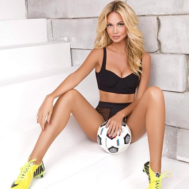 Виктория Лопырева сидит на ступеньках в черном топе в кроссовках и между ног держит мяч