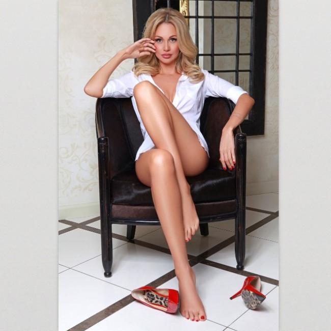 Виктория Лопырева сидит в кресле в одной рубашке, показывает голые ноги, красные туфли на высоком каблуке лежат рядом правой рукой поправляет волосы, левая лежит на подлокотнике