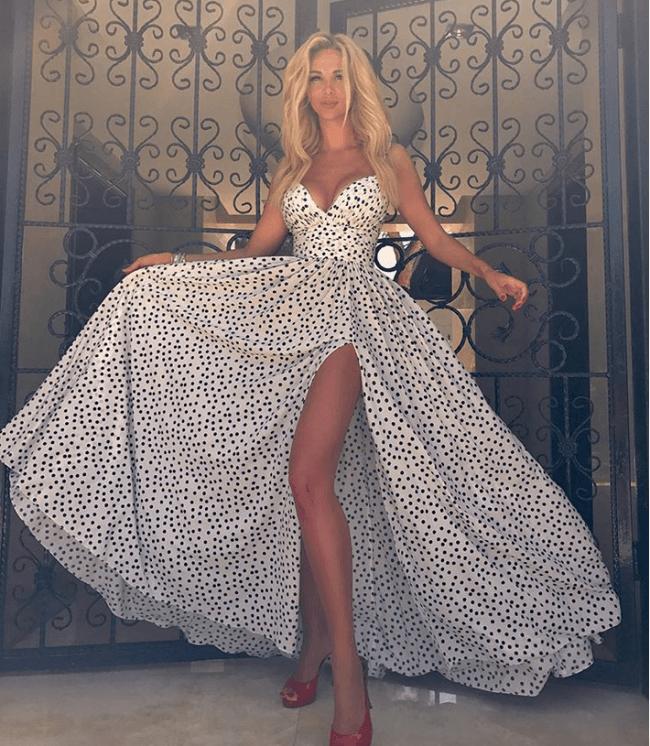 Виктория Лопырева фото в платье белом в горошек с длинным разрезом, стоит показывая стройные ножки
