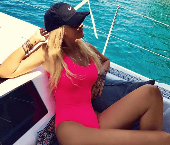 Виктория Лопырева фото в купальнике сплошном розового цвета и черной кепочке сидит в яхте
