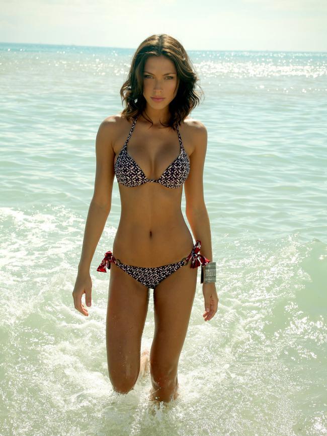 девушки на пляже в купальниках худенькая стоит по колено в воде