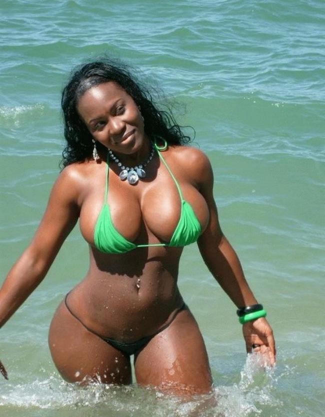 девушки в мини купальниках темнокожая красавица с бомбе зной фигурой в мини бикини стоит по колено в море, в пупке пирсинг