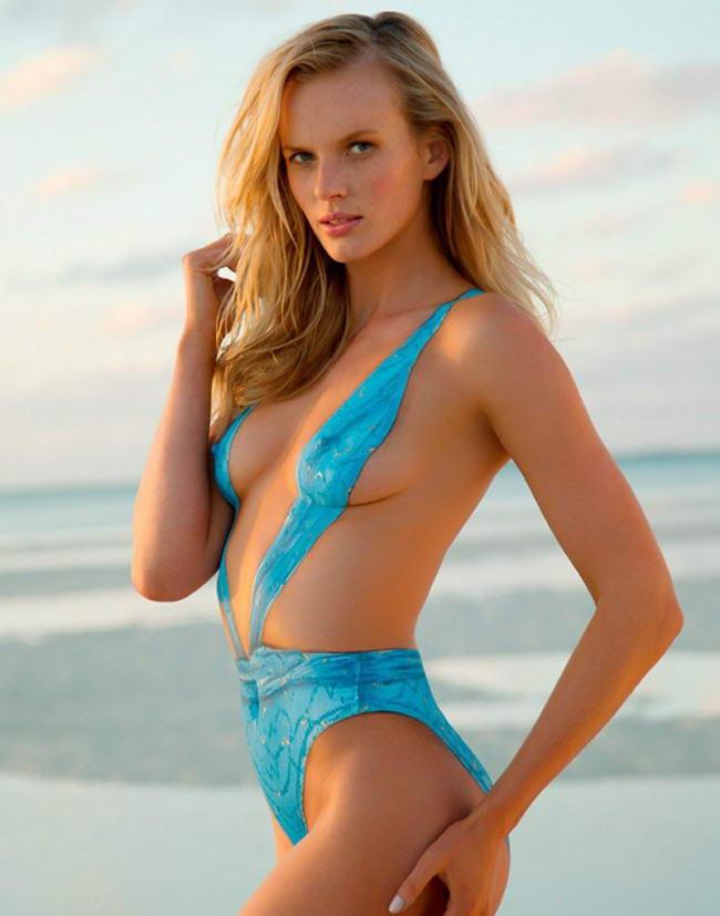 сексуальные девушки в купальниках блондинка на фоне моря в голубом купальнике стоит, левой рукой держит свою ягодицу