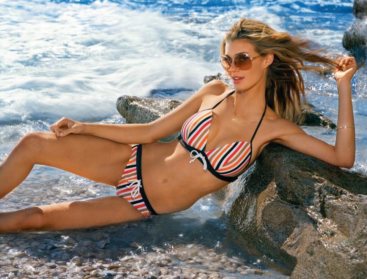 Девушки в купальниках на берегу моря в полосатом бикини в солнечных очках лежит