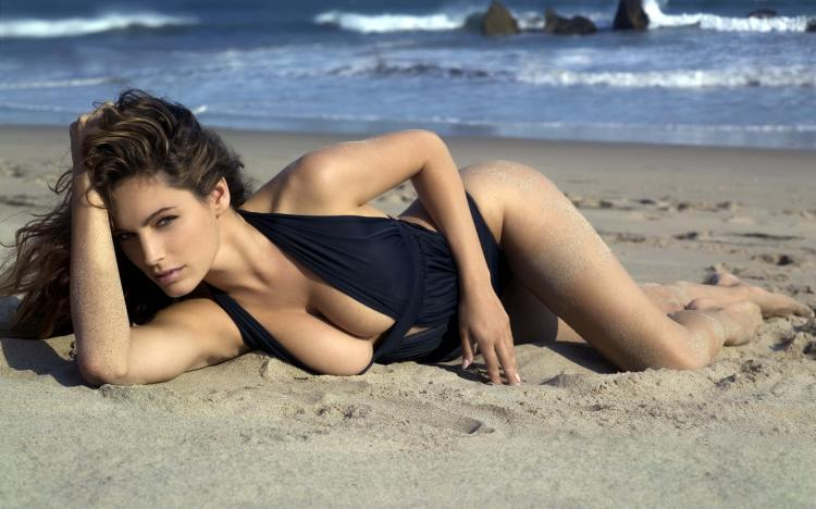 Сексуальная брюнетка в черном сплошном купальнике на песке лежит