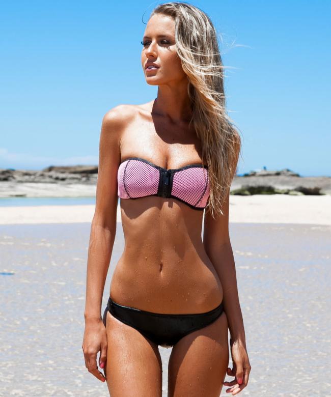 Красивая молодая блондинка с длинным волосом стоит в купальнике на пляже