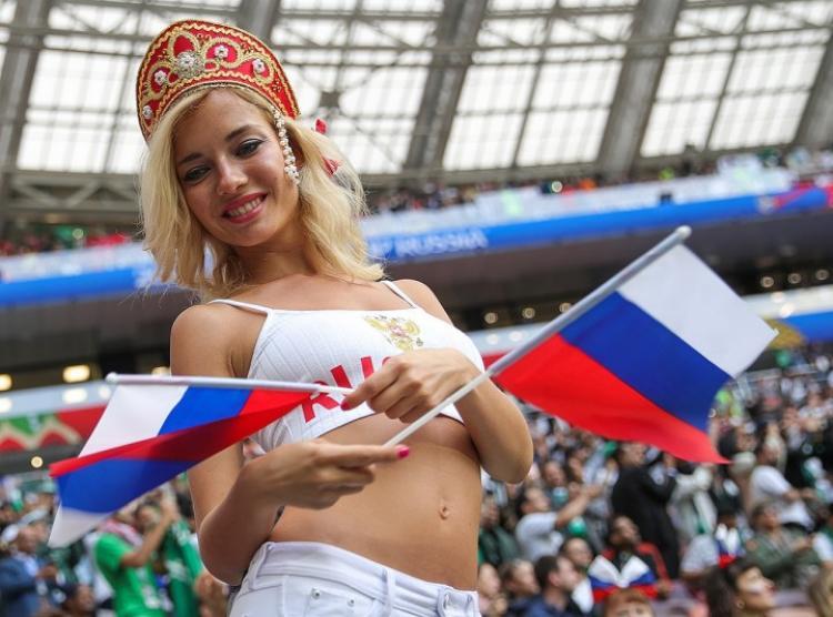 наталья немчинова болельщица на стадионе в кокошнике в коротком белом топике с открытым животиком стоит улыбается, в руках держит маленькие флаги
