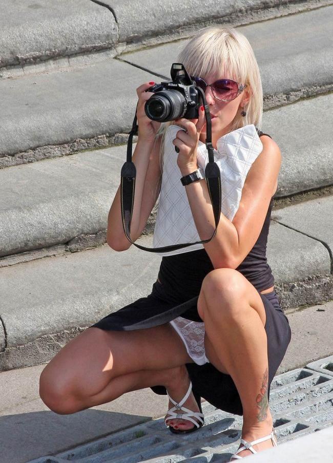 Фотографирует на корточках раздвинув ноги и показывая белые гипюровые трусики