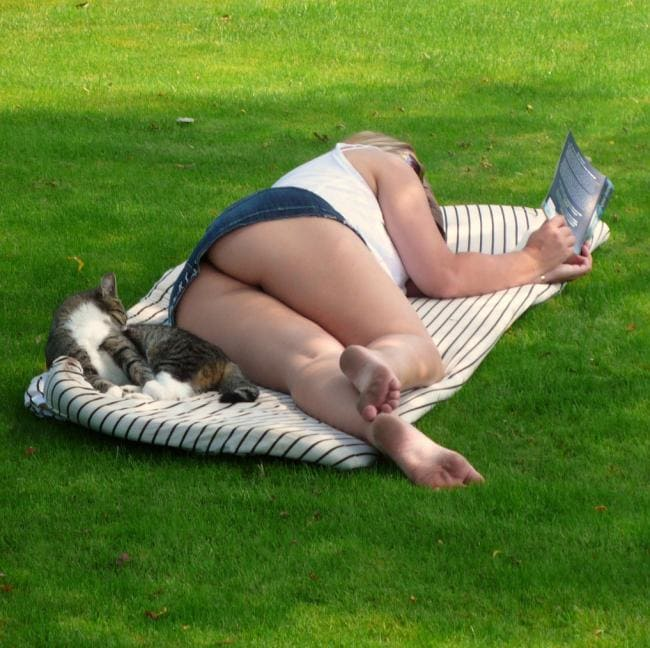 Читает лежа на травке книгу, а мы подсматриваем снизу, ступни попа