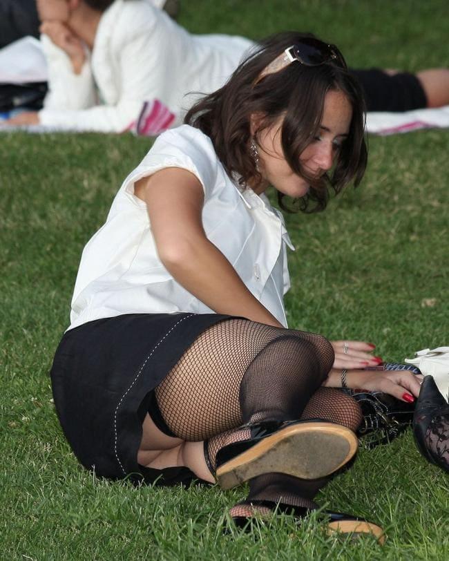 Брюнетка сидит полу боком на траве в черных в сетку чулках