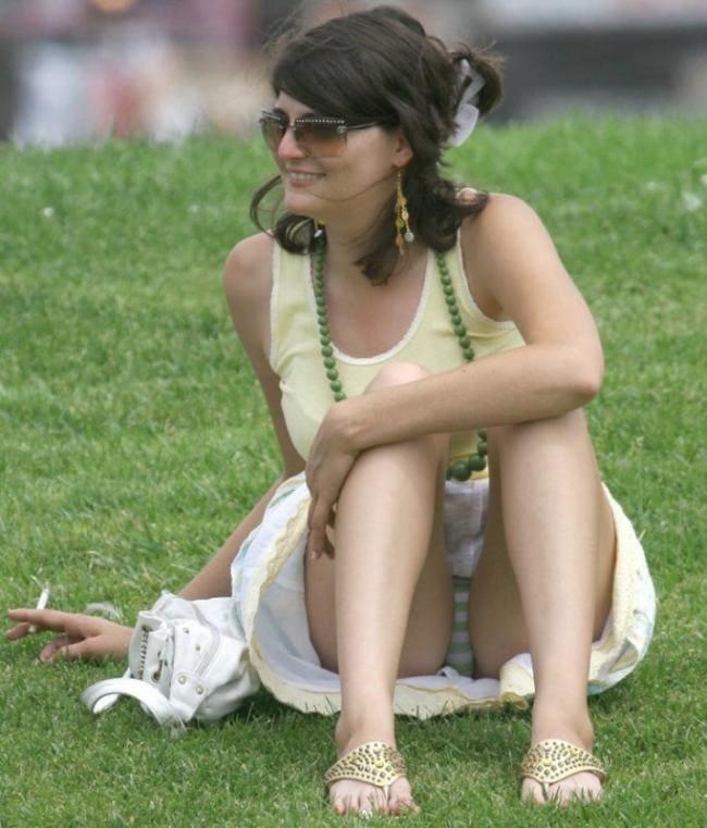 Зрелая дама с сигаретой сидит на траве, согнув ноги мы подсматриваем
