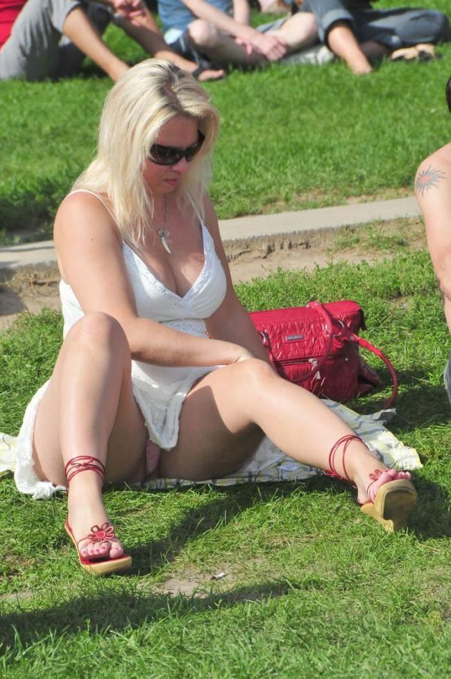 Зрелая шикарная блондинка сидит на траве растравив ноги немного согнув их в коленях, педикюр хорошо виден