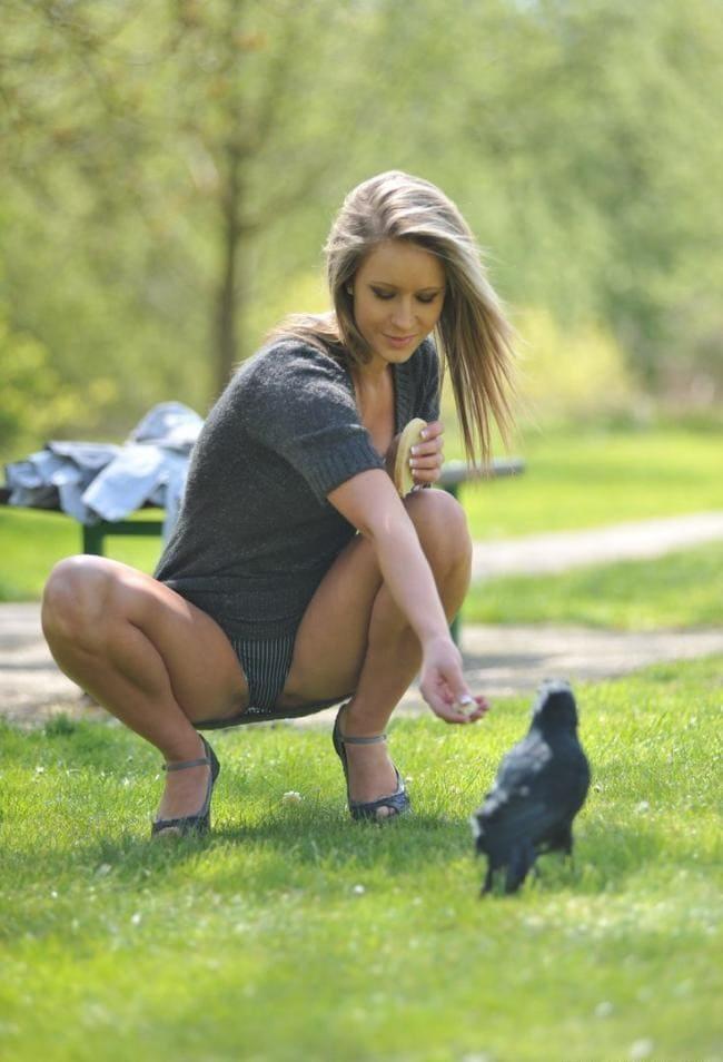 Сидеть на корточках широко расставив ноги, кормит птичку