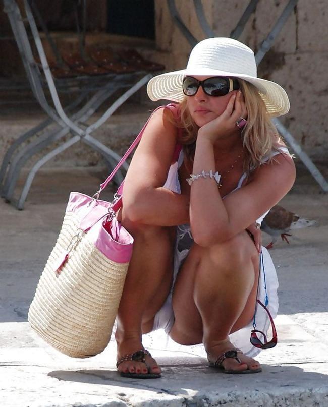 Блондинка сидит на корточках